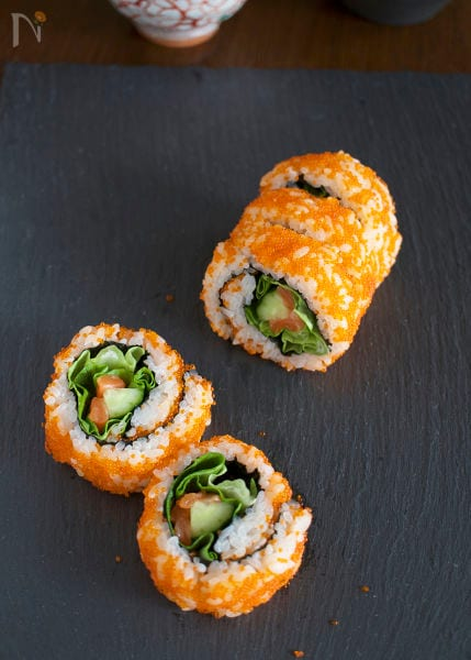 黒い皿に盛られた紅白裏巻き寿司