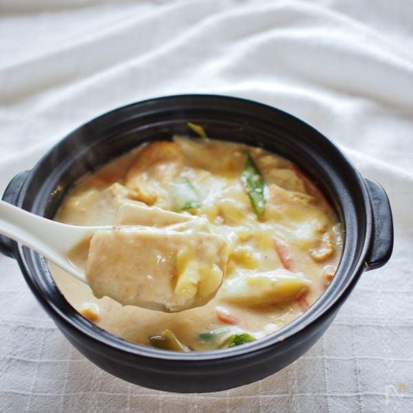 黒い土鍋で作った豆腐グラタンを、れんげですくっている様子