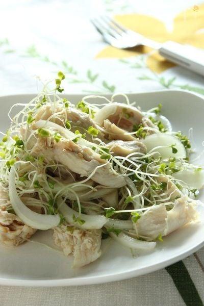 ささみと玉ねぎとブロッコリースプラウトが白いお皿の上に乗せられている
