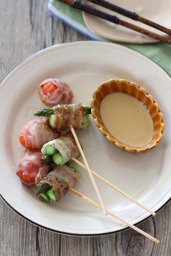 こんがりと焼けたアスパラとトマトの豚串焼きがプレートの上にのっている様子